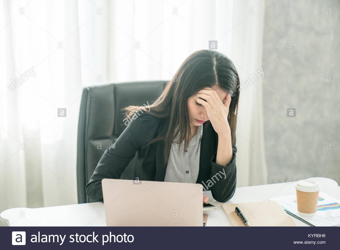 Sensazione di stanchezza e sottolinea una giovane donna mentre è seduto al suo posto di lavoro sul luogo di Immagini Stock