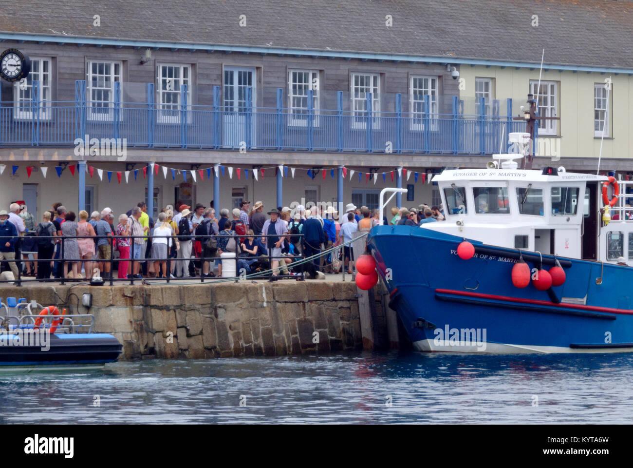 Seniors caucasica accodamento in Hugh Town Harbour Quay per imbarcarsi sul traghetto per passeggeri, Hugh Town, St Marys, isole Scilly, Cornwall, Regno Unito Foto Stock