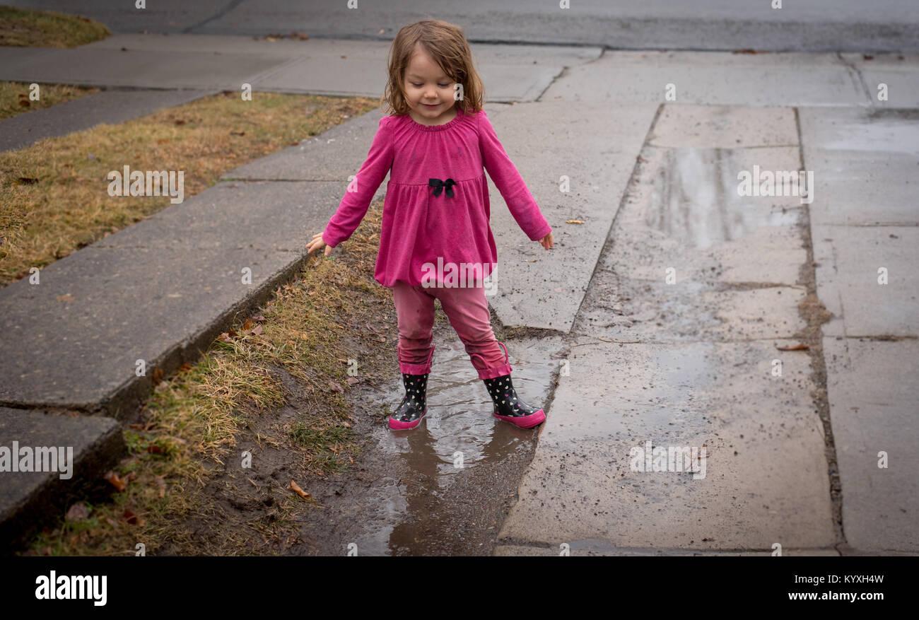 Un bambino che indossa una camicia rosa, rosa slip e rosa stivali da pioggia sorge in una pozza di fango in un vialetto Immagini Stock