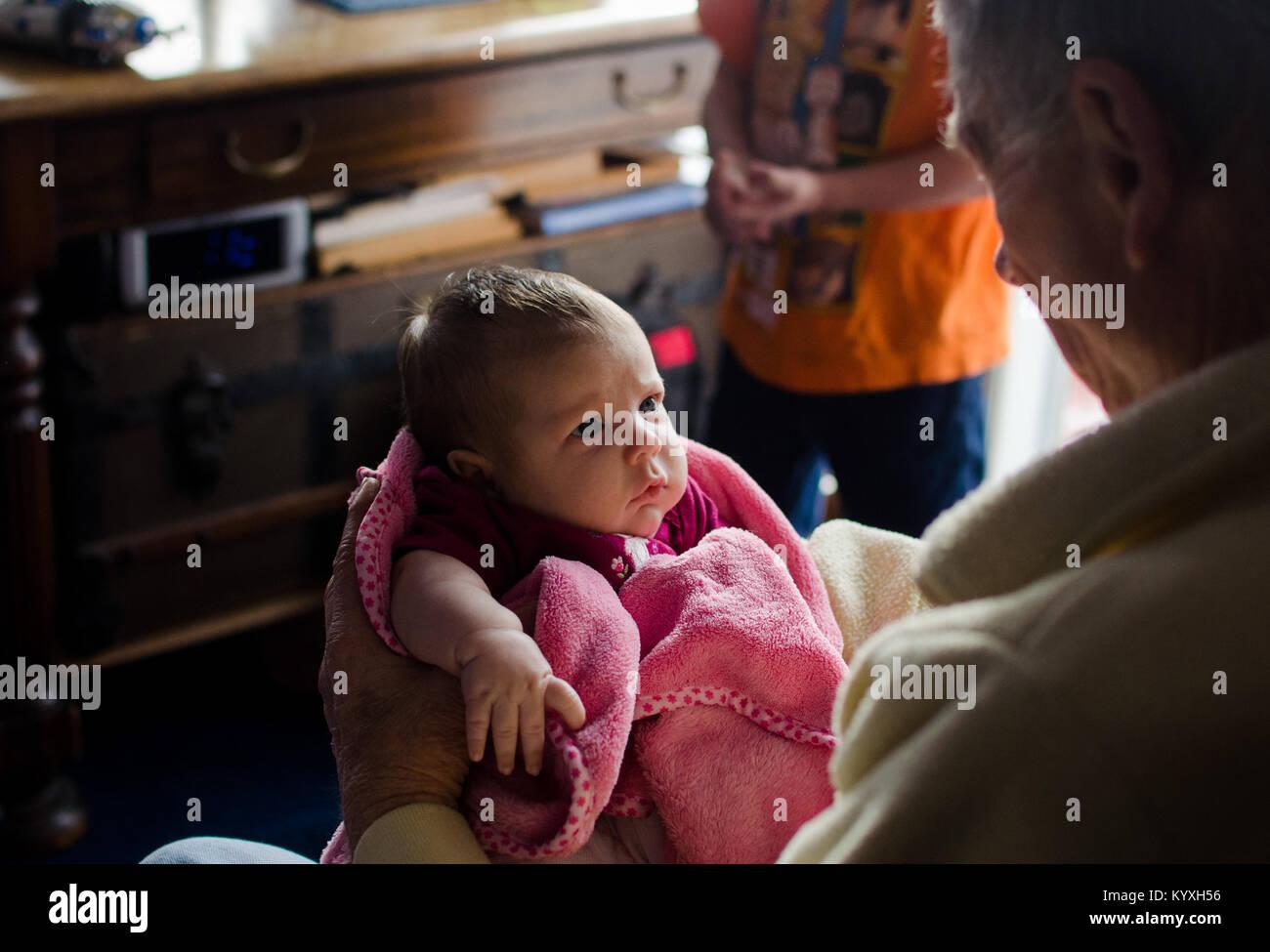 Un nonno mantiene i suoi due mesi al nipote in un blanket di rosa. Immagini Stock