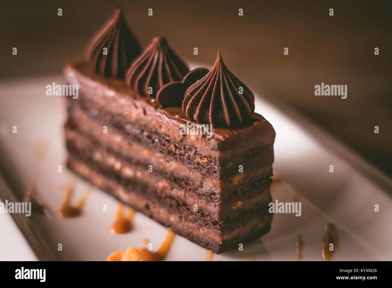 Primo piano di una torta al cioccolato su una piastra bianca sulla luce naturale Immagini Stock