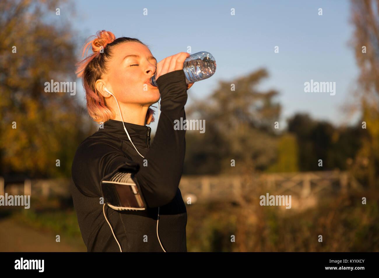 Donna acqua potabile mentre si ascolta la musica al parco Immagini Stock