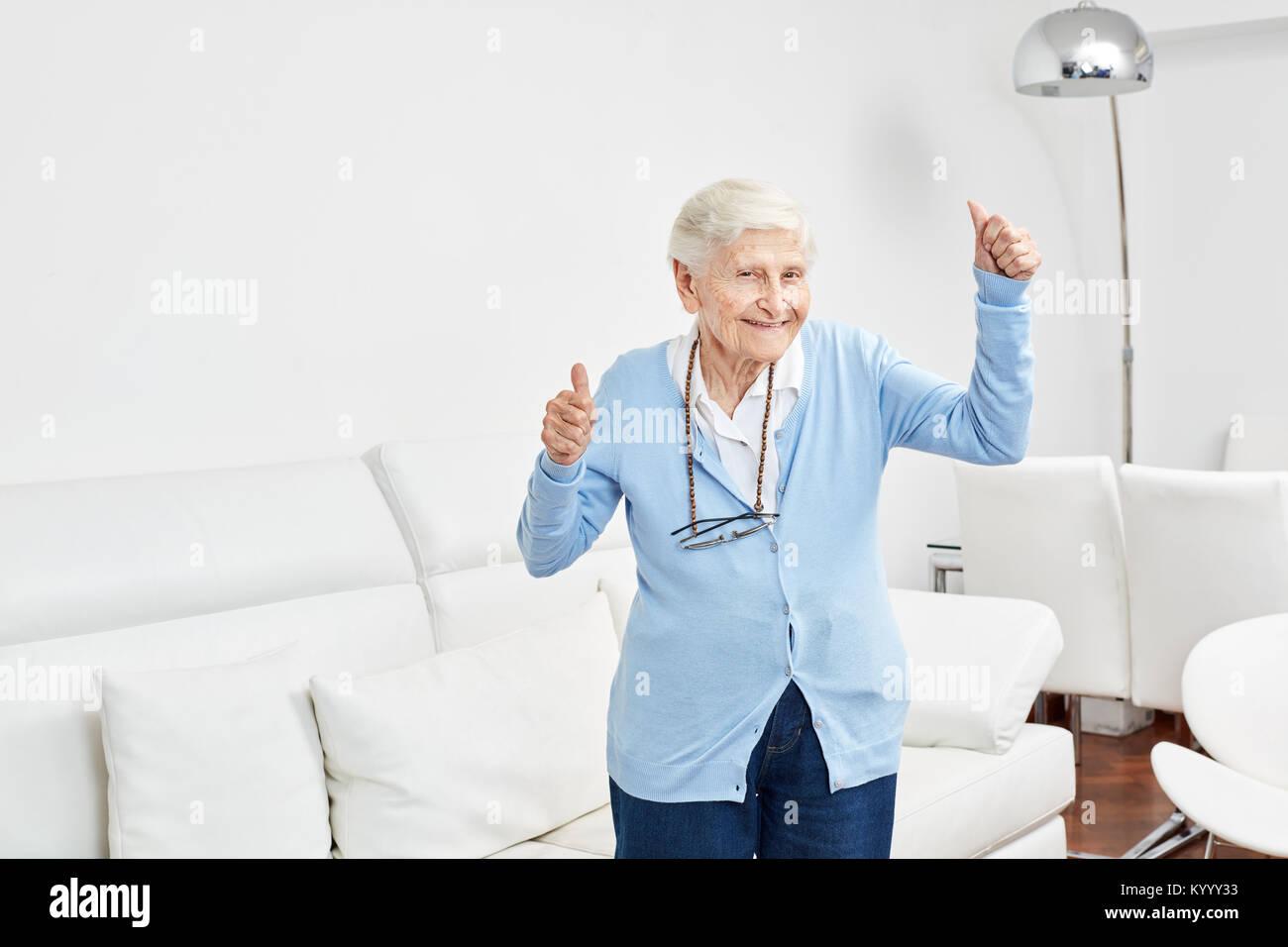 Vecchia donna gioisce di vitalità e joie de vivre e tiene le dita incrociate Immagini Stock