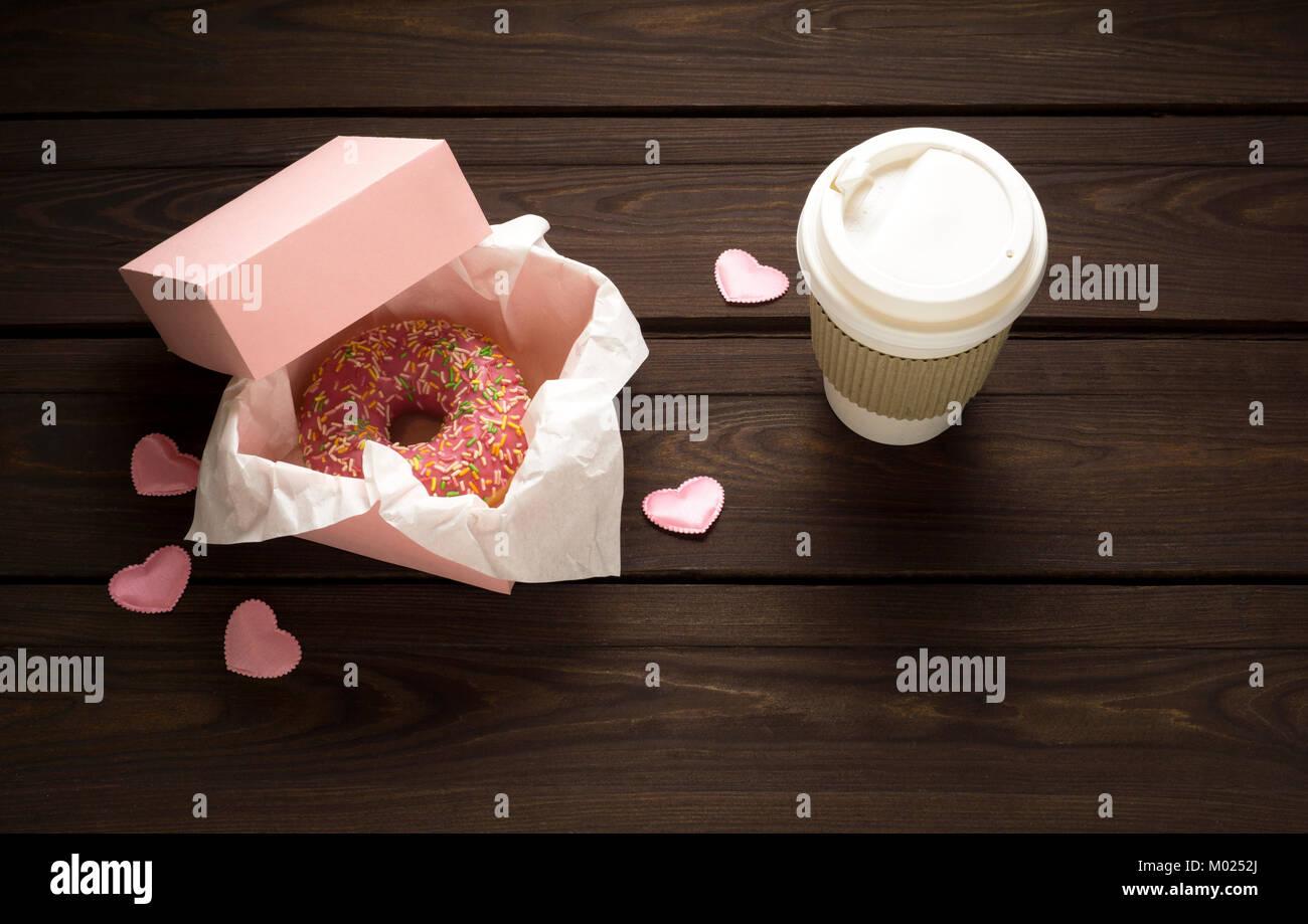Creative valentine concetto foto della ciambella con take away caffè su sfondo di legno. Immagini Stock