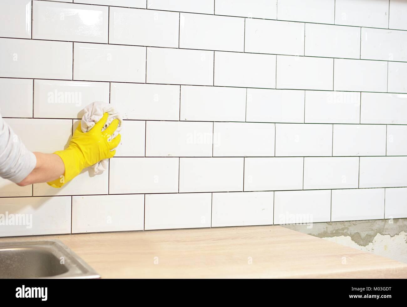 La finitura il tiling della cucina con piastrelle bianche Immagini Stock
