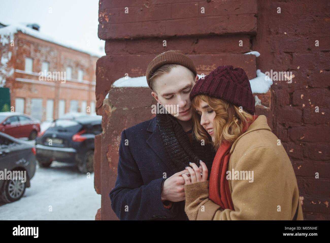 Giovane uomo e donna abbracciando vicino a Brick angolo dell'edificio. Inverno street. Privacy in luoghi appartati Immagini Stock