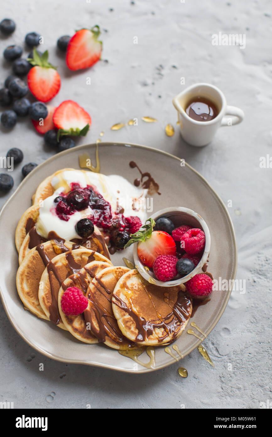 Pancake con frutta fresca e salsa al cioccolato e sciroppo d'acero Immagini Stock