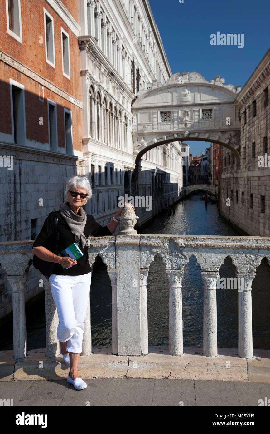 In dotazione con la sua guida Michelin prenota, un anziano turista in posa di fronte al ponte dei sospiri a Venezia Immagini Stock