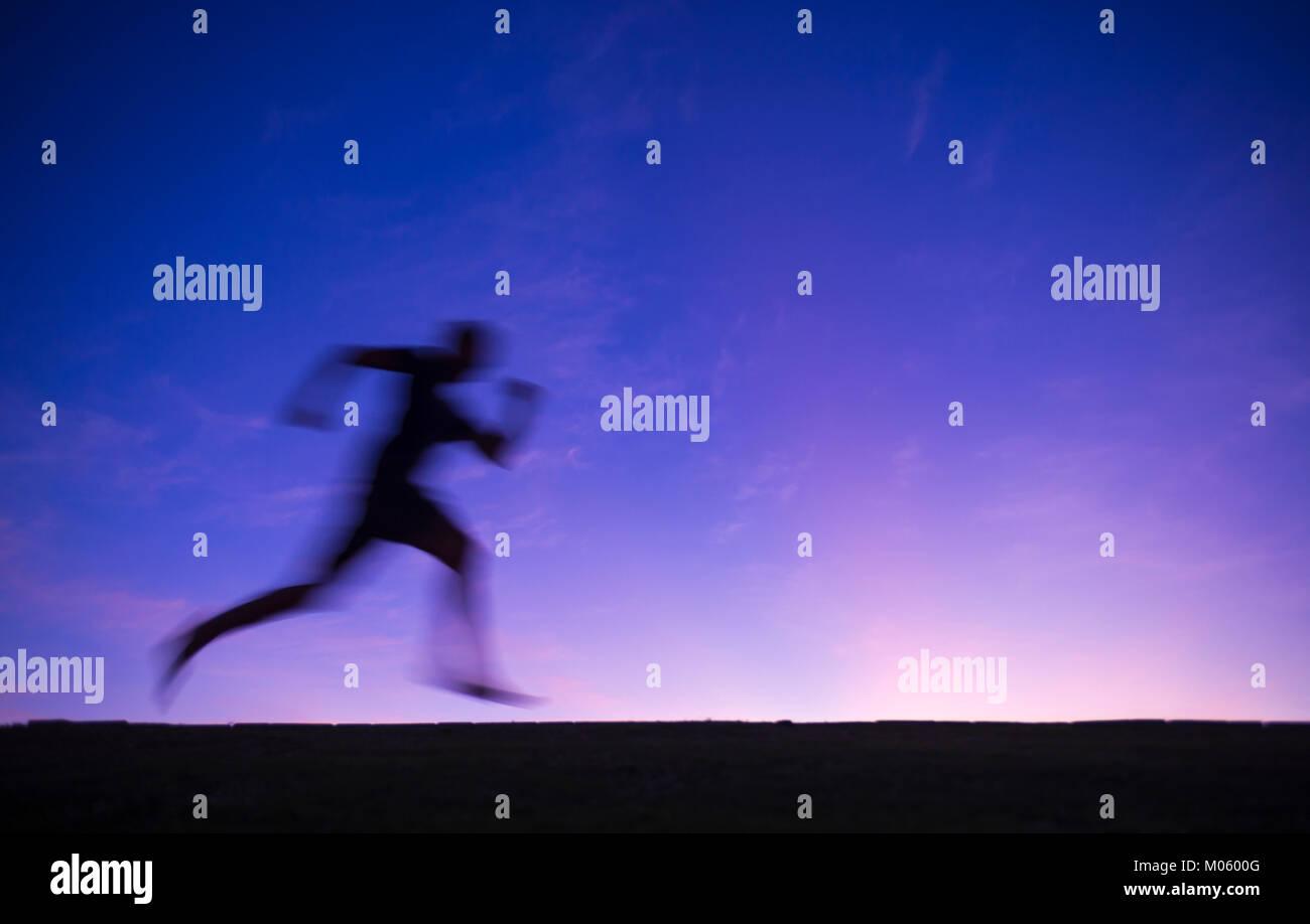 Silhouette di sfocatura di un runner passando attraverso un crepuscolo viola del tramonto sullo sfondo del cielo Immagini Stock