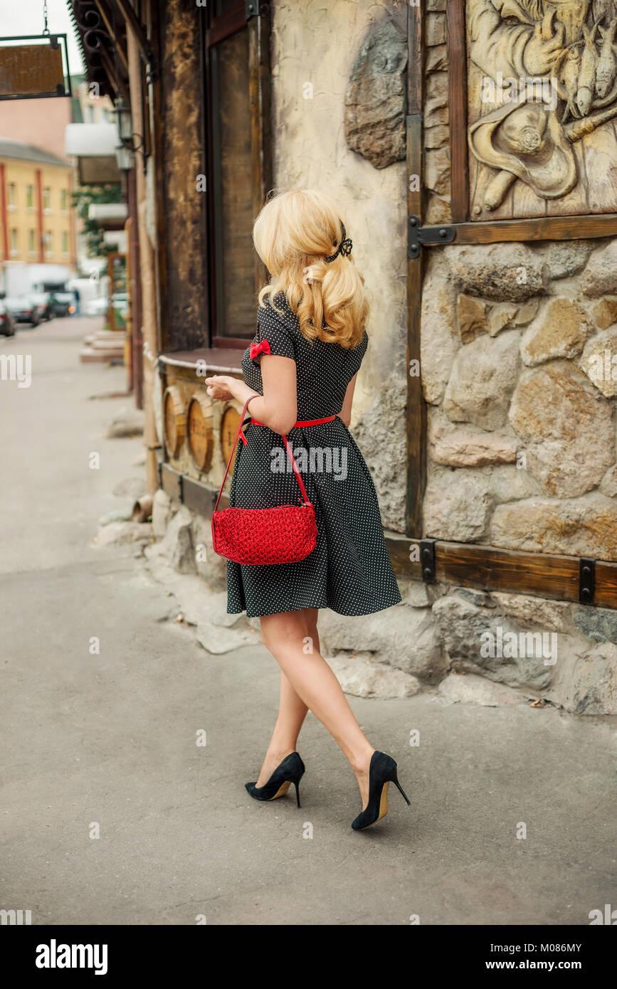 Donna bionda con un vestito e tacchi camminare per la strada