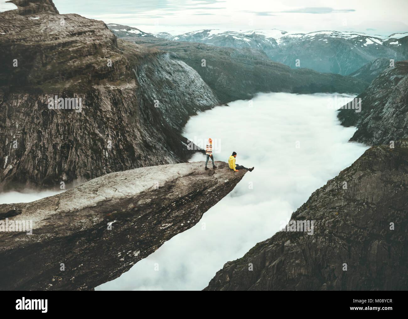 Giovane uomo e donna sulla scogliera Trolltunga in Norvegia al di sopra delle nuvole di amore e di emozioni di viaggio Immagini Stock