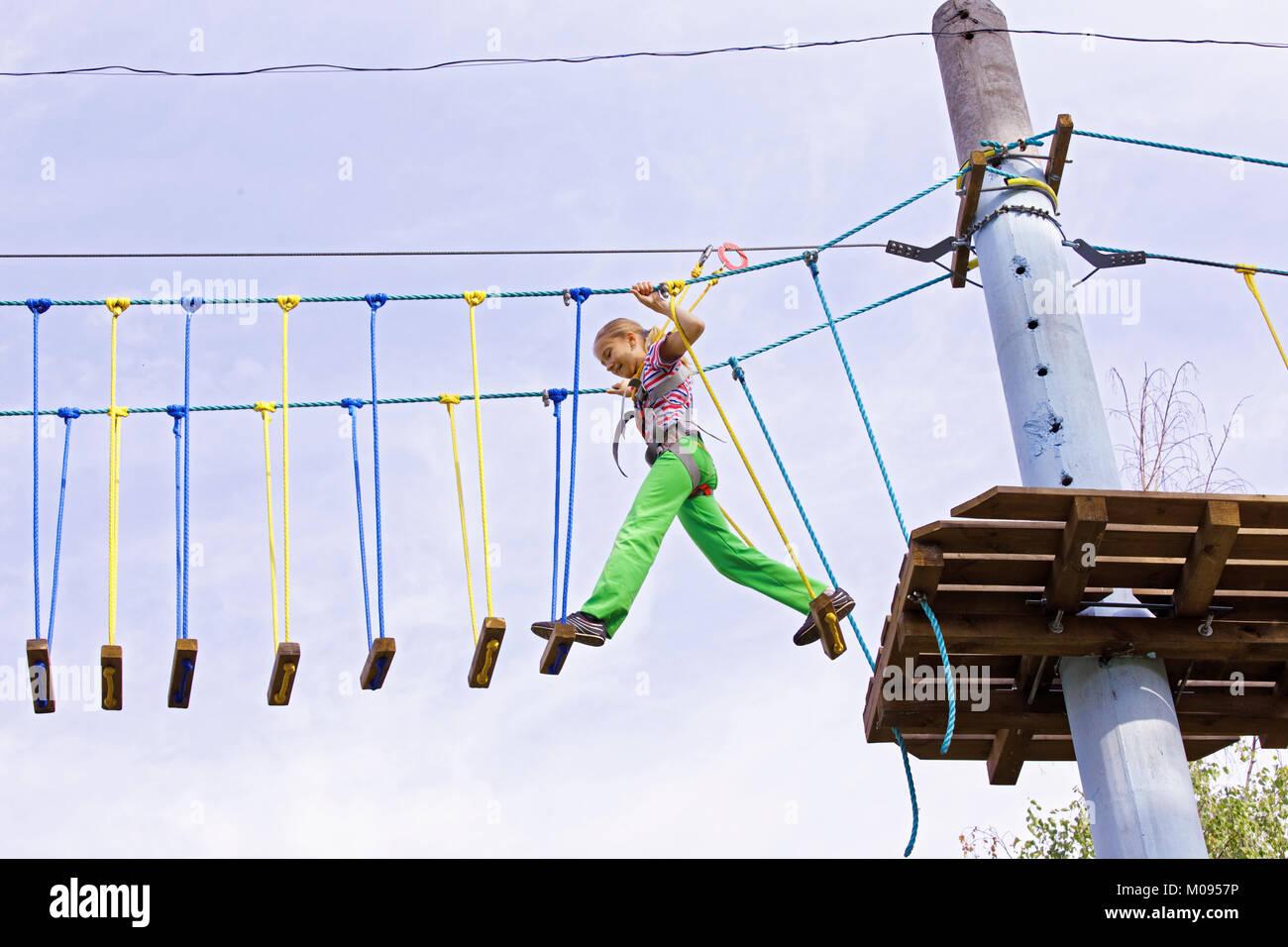 Una ragazza adolescente si muove con fiducia su tavole oscillanti in altezza in una corda park. Coraggio e superare Immagini Stock