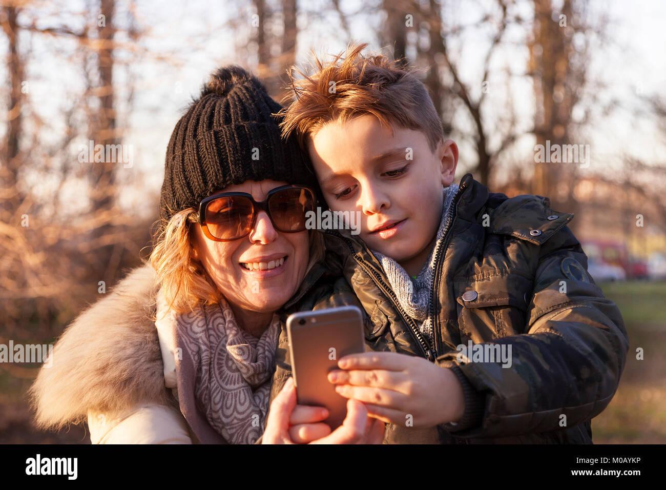 La madre e il figlio prende un selfie in un parco pubblico in inverno. concetto di persone aventi fun Immagini Stock