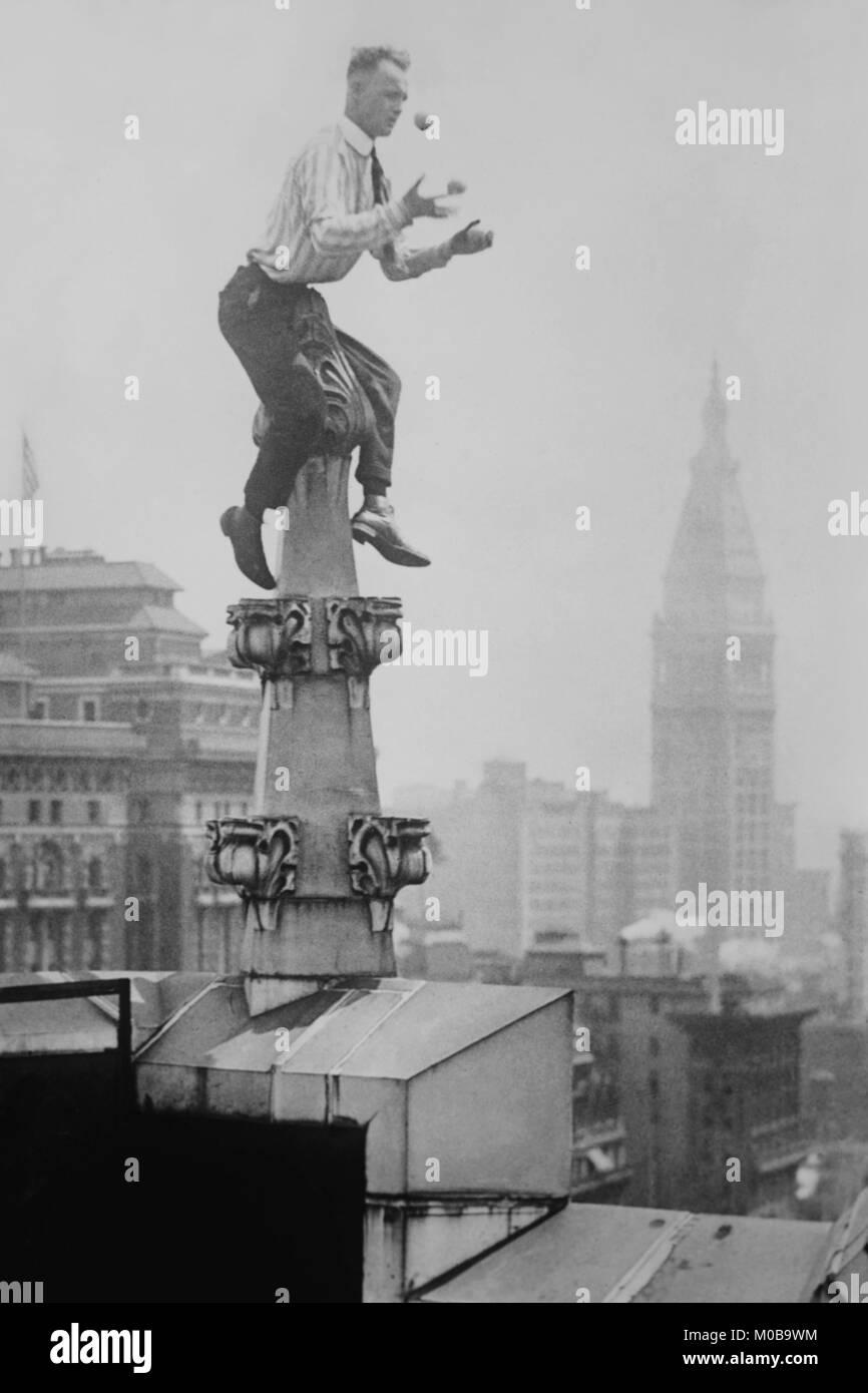 La Reynolds giocola sfere sul pinnacolo di un tetto alto sopra la città di New York Immagini Stock
