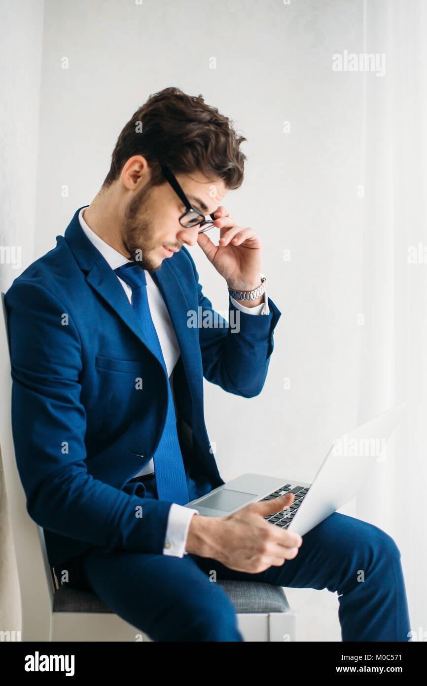 Giovane imprenditore lavora con il computer portatile in ufficio Immagini Stock