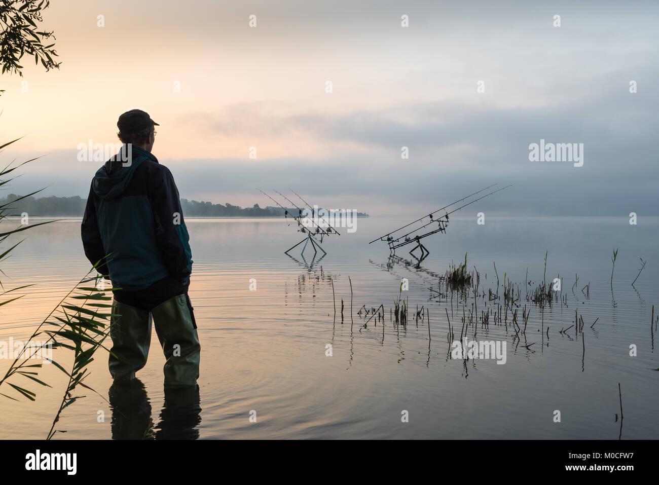 Le avventure di pesca, la pesca alla carpa. La mattina presto con la nebbia e fisherman con alta stivali di gomma Immagini Stock