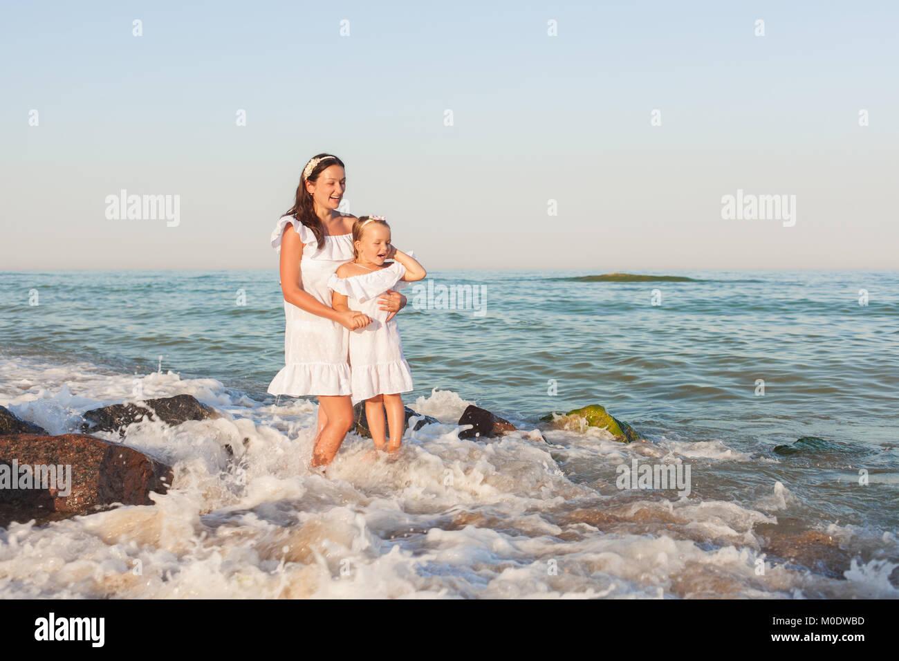 6bd563b9cbf0 Mamma e figlia in bianco vestiti in stand by il mare tra le onde ...
