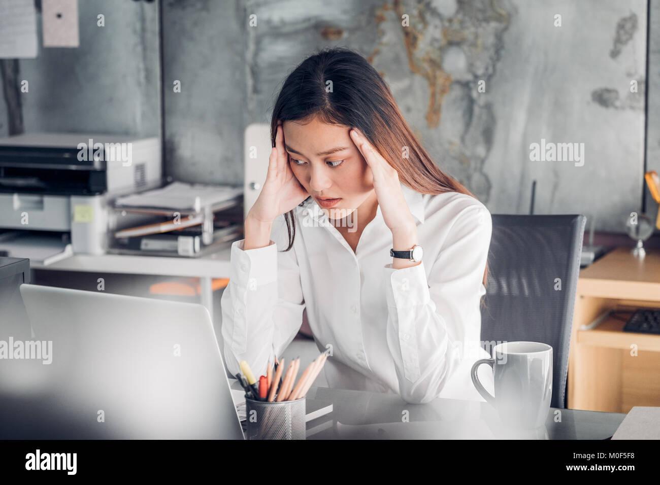 Frustrati Asian imprenditrice coprire il suo volto con due mani e sento sconvolto dal lavoro nella parte anteriore Immagini Stock