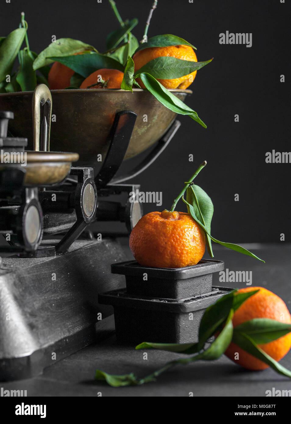 Un mazzetto di fresco succosa clementine con foglie verdi in un scalepan e su una tavola nera Foto Stock