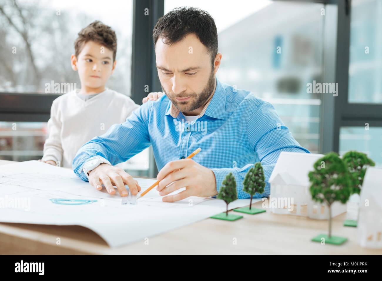 Occupato architetto prestando alcuna attenzione al suo piccolo figlio Immagini Stock