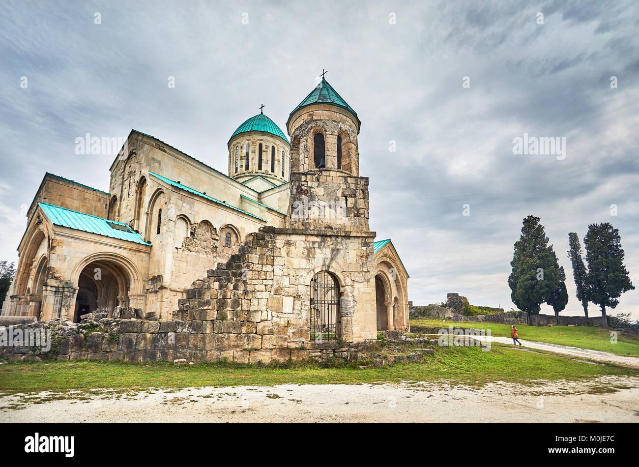 La donna per raggiungere a piedi la torre della cappella della chiesa Bagrati a cielo nuvoloso in Kutaisi, Georgia Immagini Stock