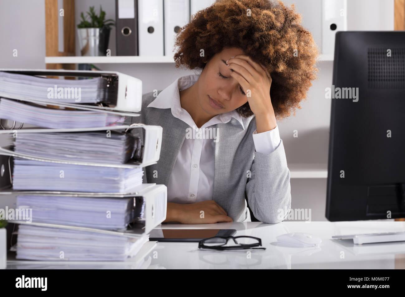 Stressante Afro American imprenditrice seduta in ufficio con impilati di file Immagini Stock