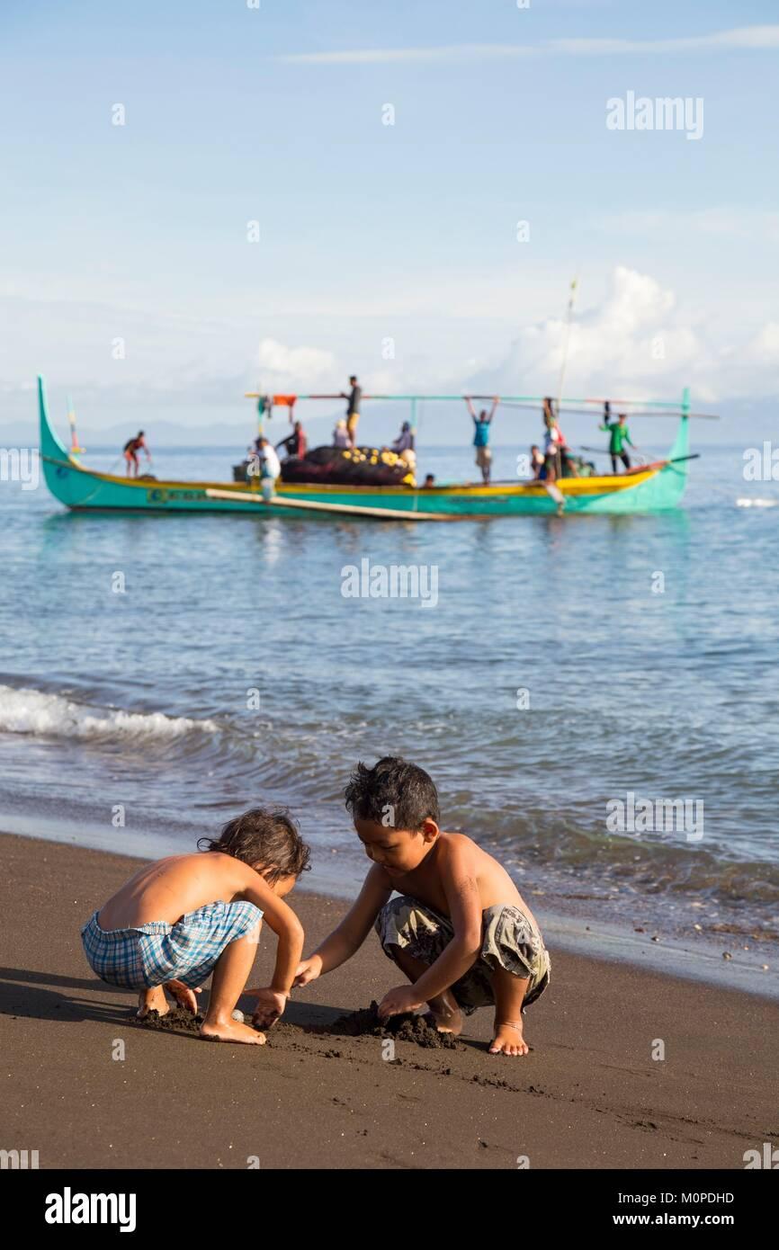 Filippine,Luzon,Albay provincia,Tiwi,Sogod beach,i bambini giocando sulla sabbia con un ringnet barca da pesca tornando in background Foto Stock