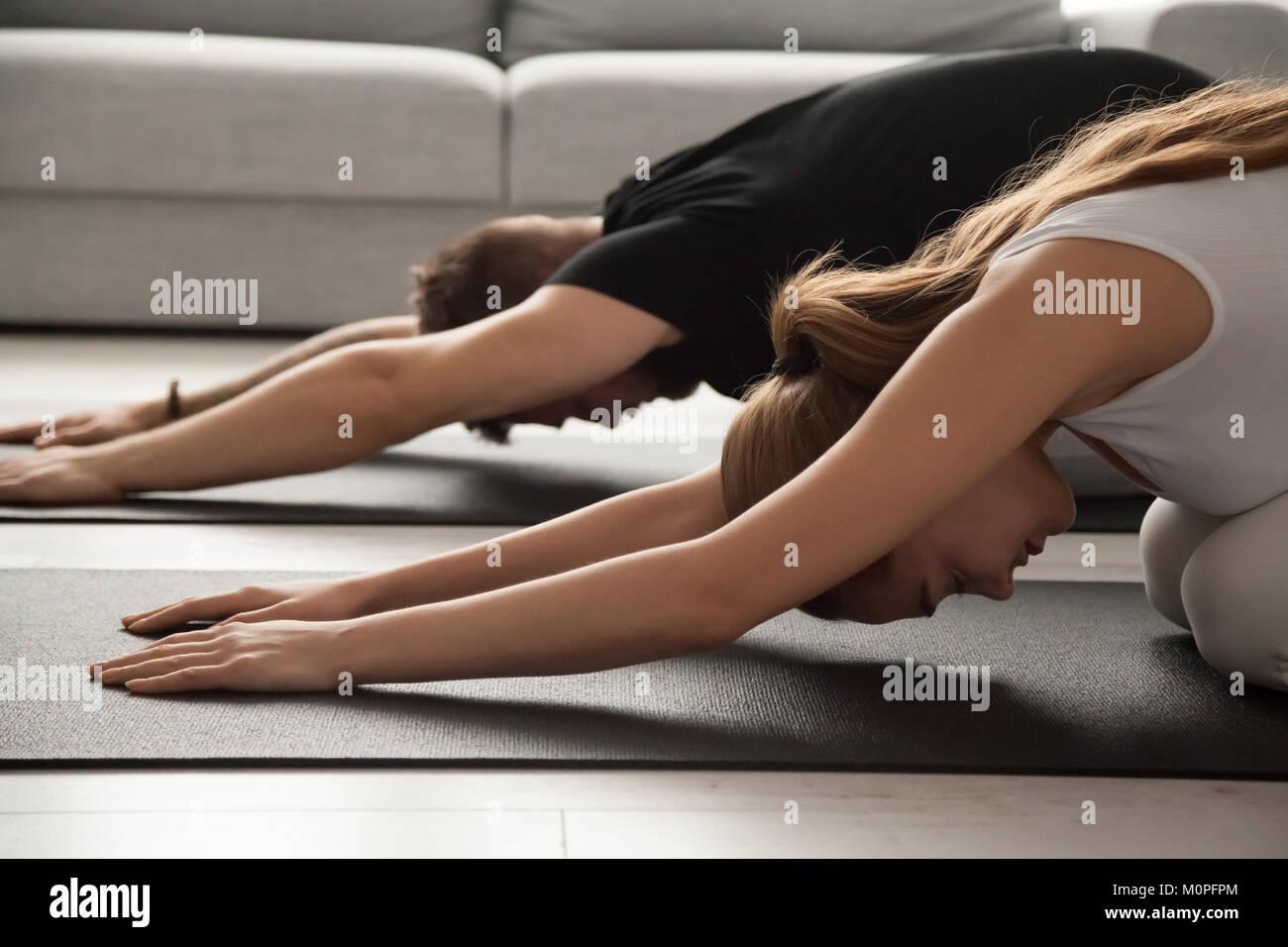 Matura la pratica dello yoga nel bambino pone rilassante su mat insieme Immagini Stock