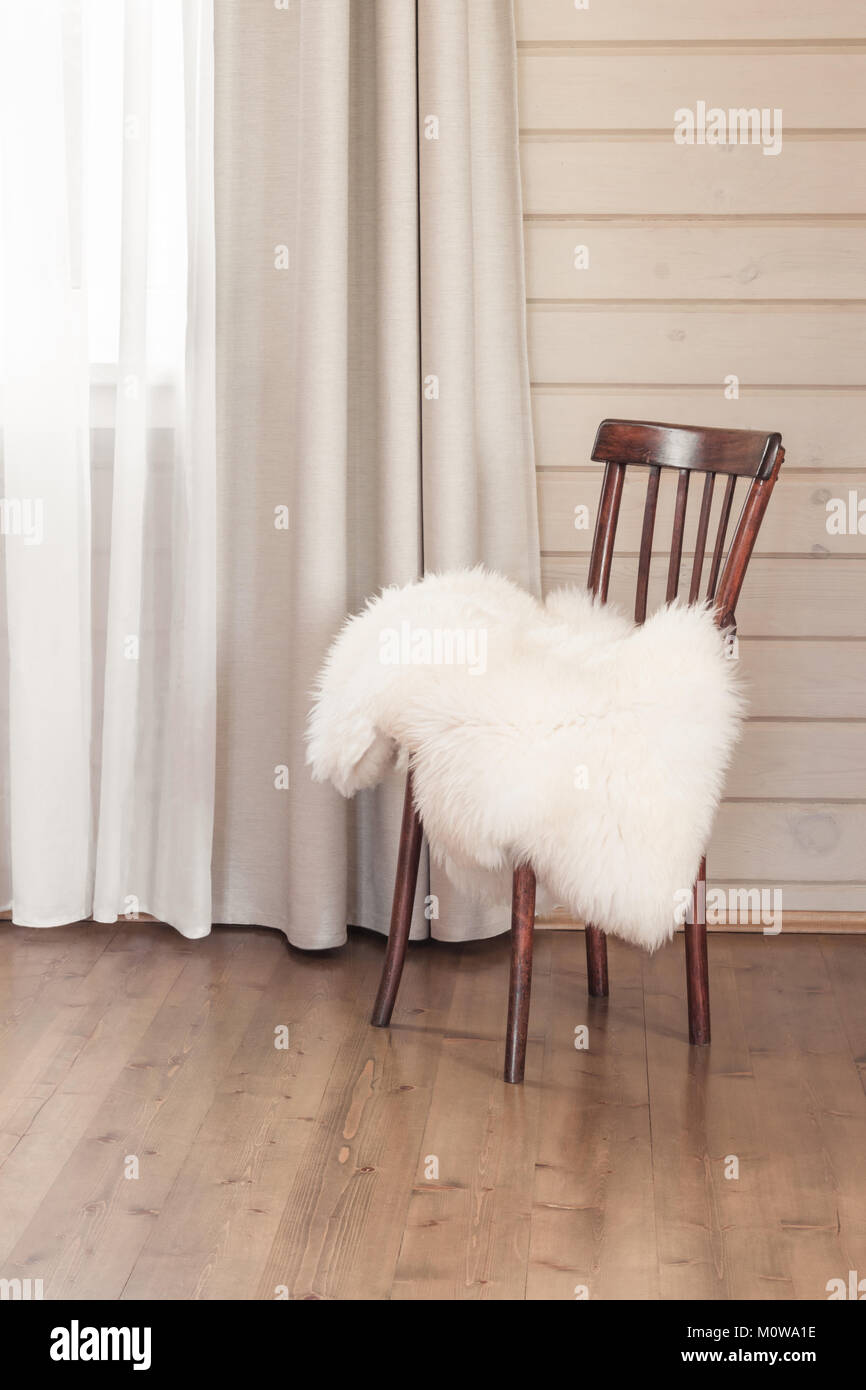 Legno sedia vintage e pelliccia su di esso in casa rustica