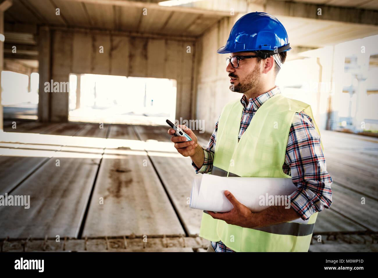 Architetto maschio comunicando su un walkie-talkie presso il sito Immagini Stock