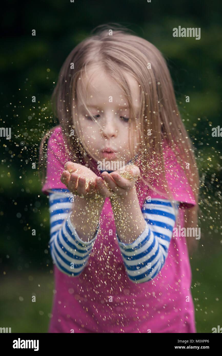 Ragazza di soffiaggio glitter oro mani off Immagini Stock