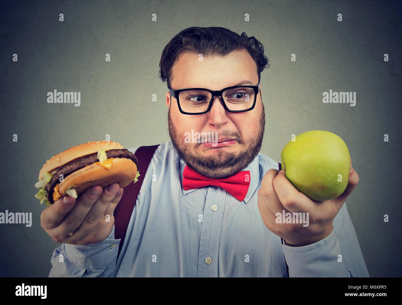Il sovrappeso uomo holding hamburger e mela verde avendo problemi con la dieta scelta. Immagini Stock