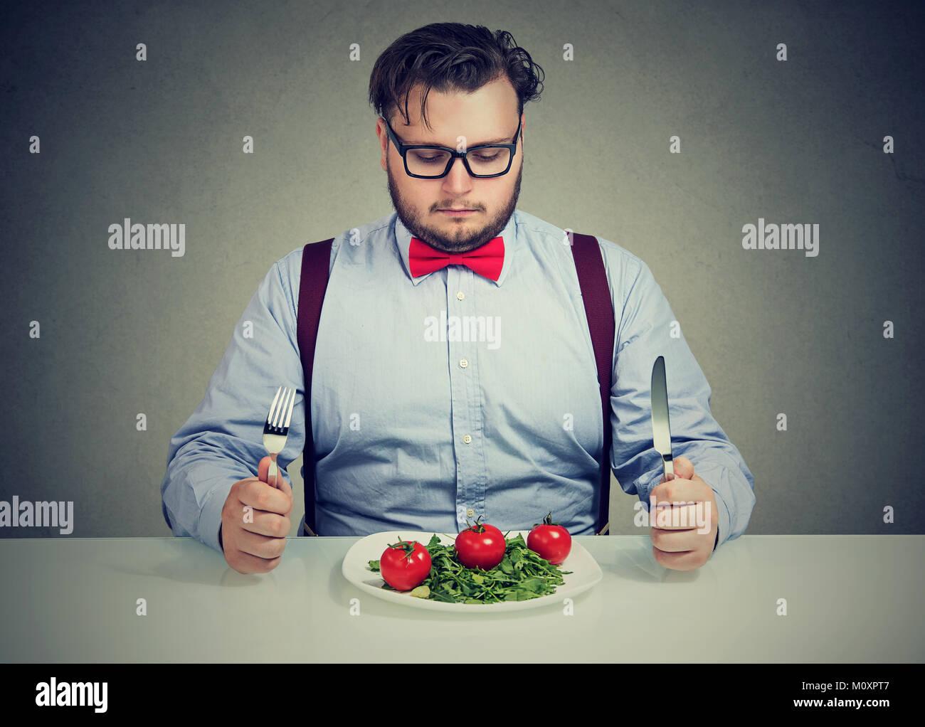 Giovane uomo sovrappeso concentrato su insalata sana cercando di perdere peso. Immagini Stock