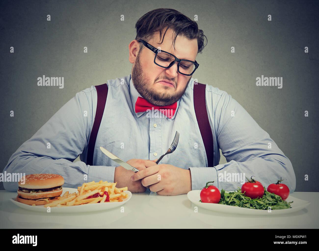 Il sovrappeso uomo in abito formale guardando insalata†con odio mentre succo di craving hamburger. Immagini Stock