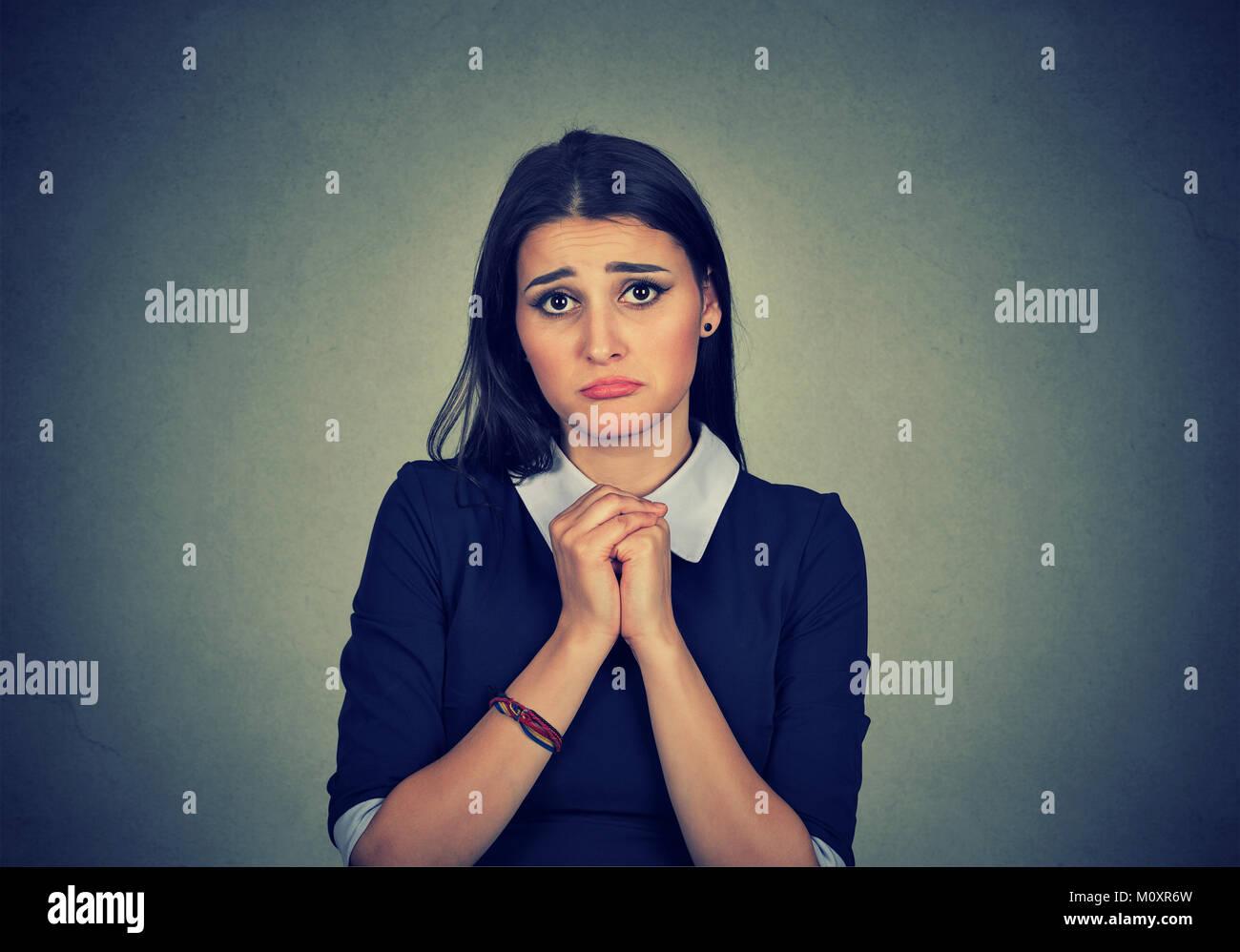 Giovane donna formale cercando colpevole in telecamera a mendicare di perdonare. Immagini Stock