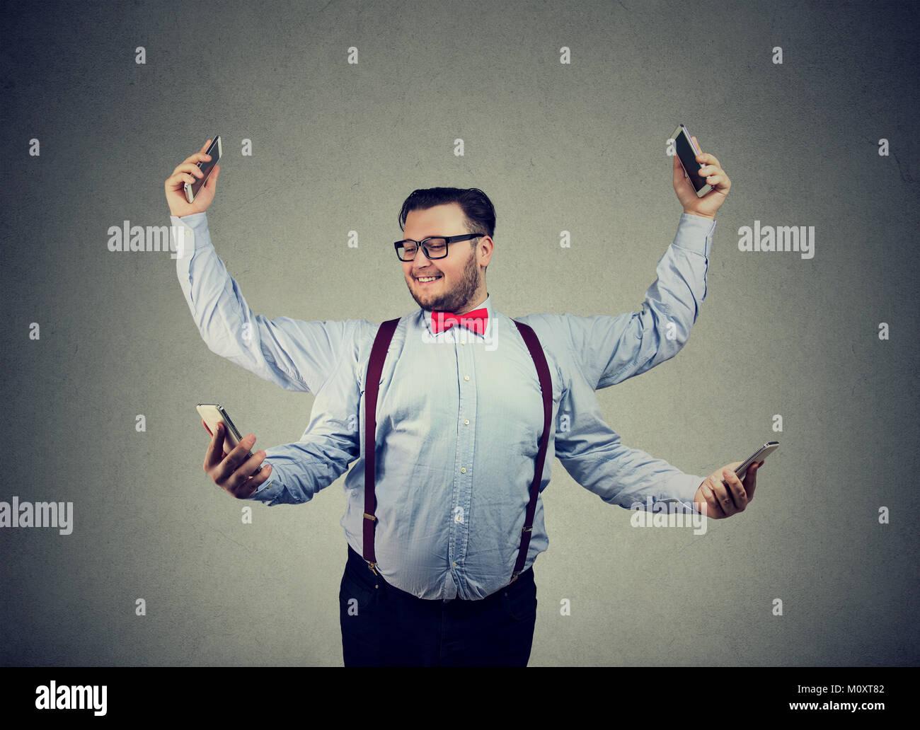 Chunky giovane uomo in abbigliamento formale avente quattro bracci e tramite smartphone multitasking. Immagini Stock