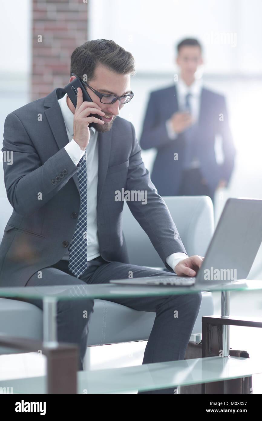 Ritratto di imprenditore parlando al telefono cellulare in ufficio Immagini Stock