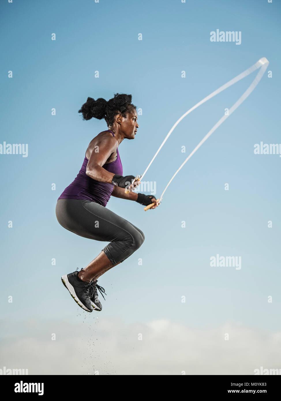Nero donna salto con la corda nel cielo Foto Stock