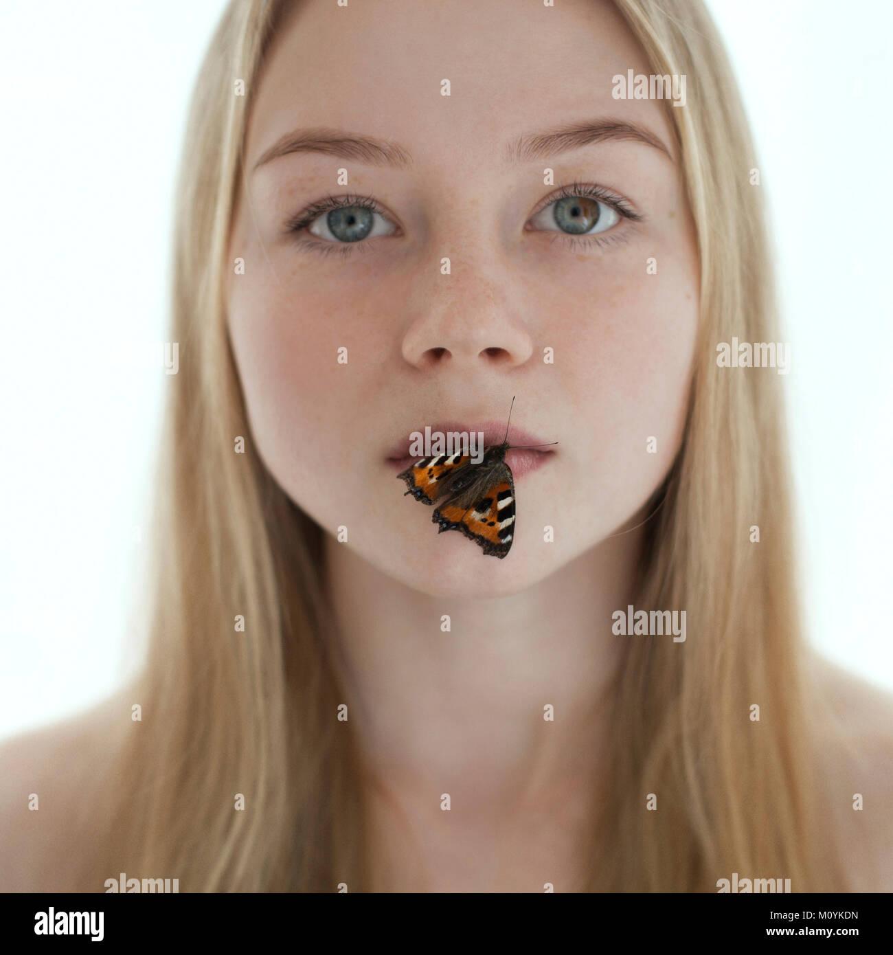Farfalla sulle labbra di soggetti di razza caucasica ragazza adolescente Foto Stock