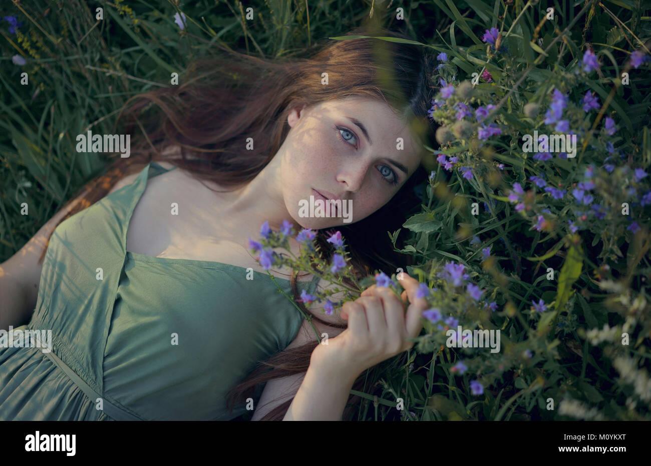 La donna caucasica posa in erba con fiori di campo Foto Stock