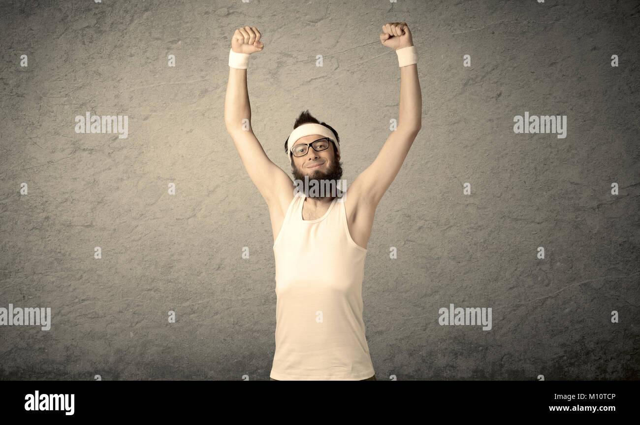 Un giovane uomo con la barba, headstrap e bicchieri in posa di fronte dello sbozzato muro grigio Sfondo, immaginando Immagini Stock