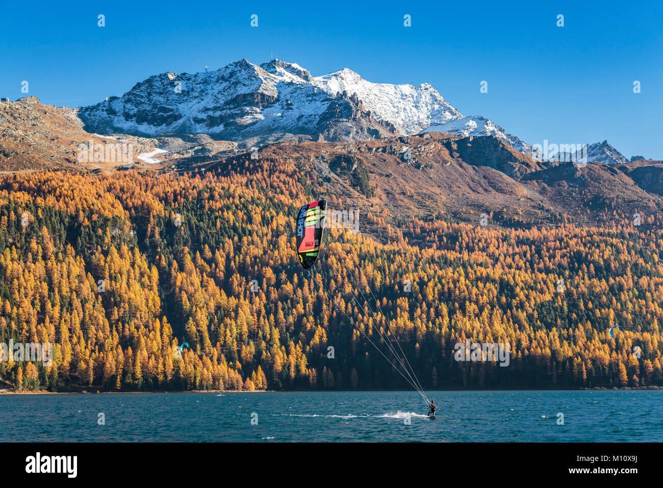 Wind surf sul lago di Silvaplana con la caduta delle foglie colore in larice alberi in Engadina, Graubuden, Svizzera, Immagini Stock