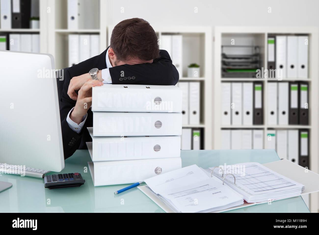 Imprenditore di dormire sulla pila di cartelle in ufficio Immagini Stock