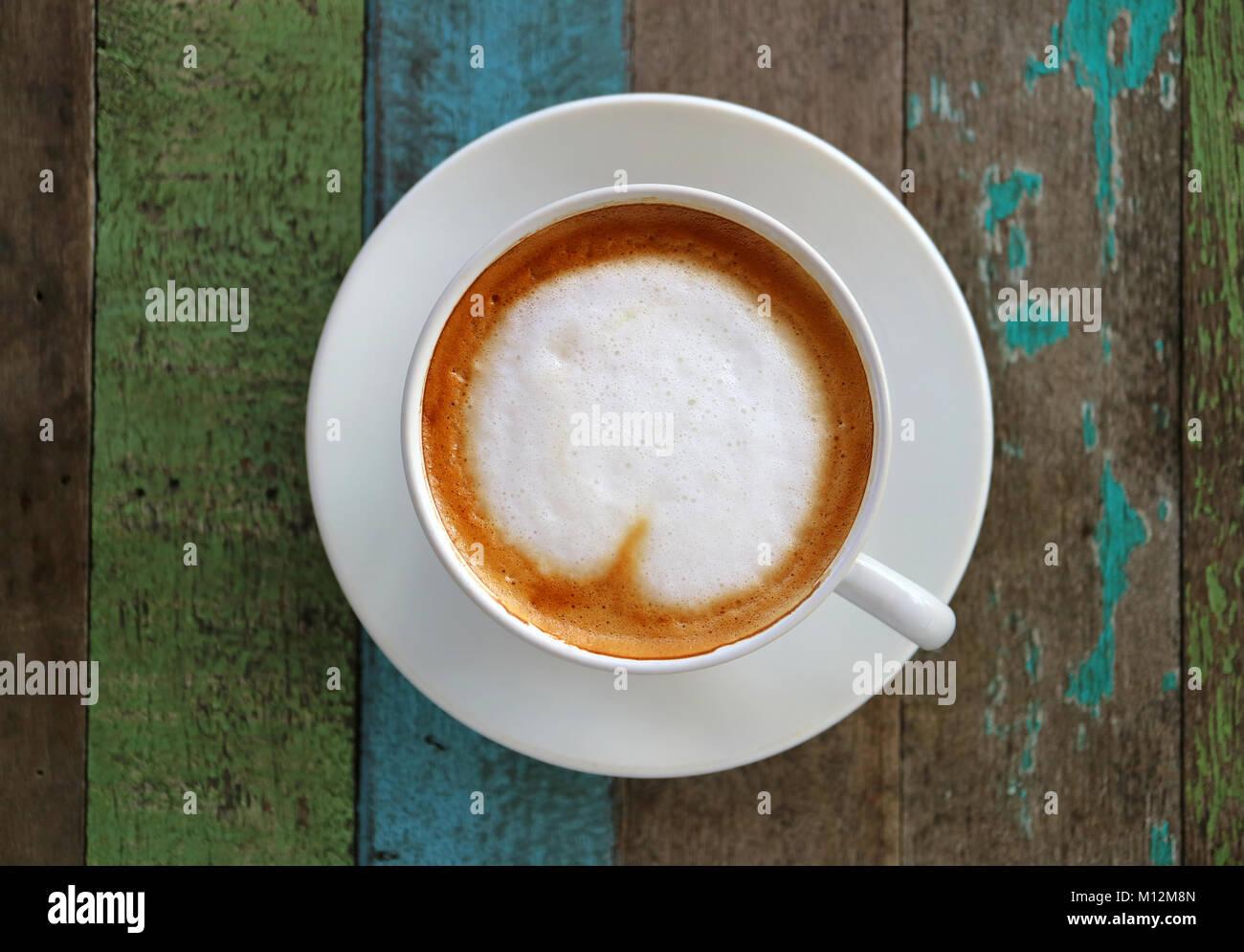 Caffè caldo con a forma di cuore ad Latte Art in una tazza bianca su colorato stile rustico tavolo in legno,vista Immagini Stock