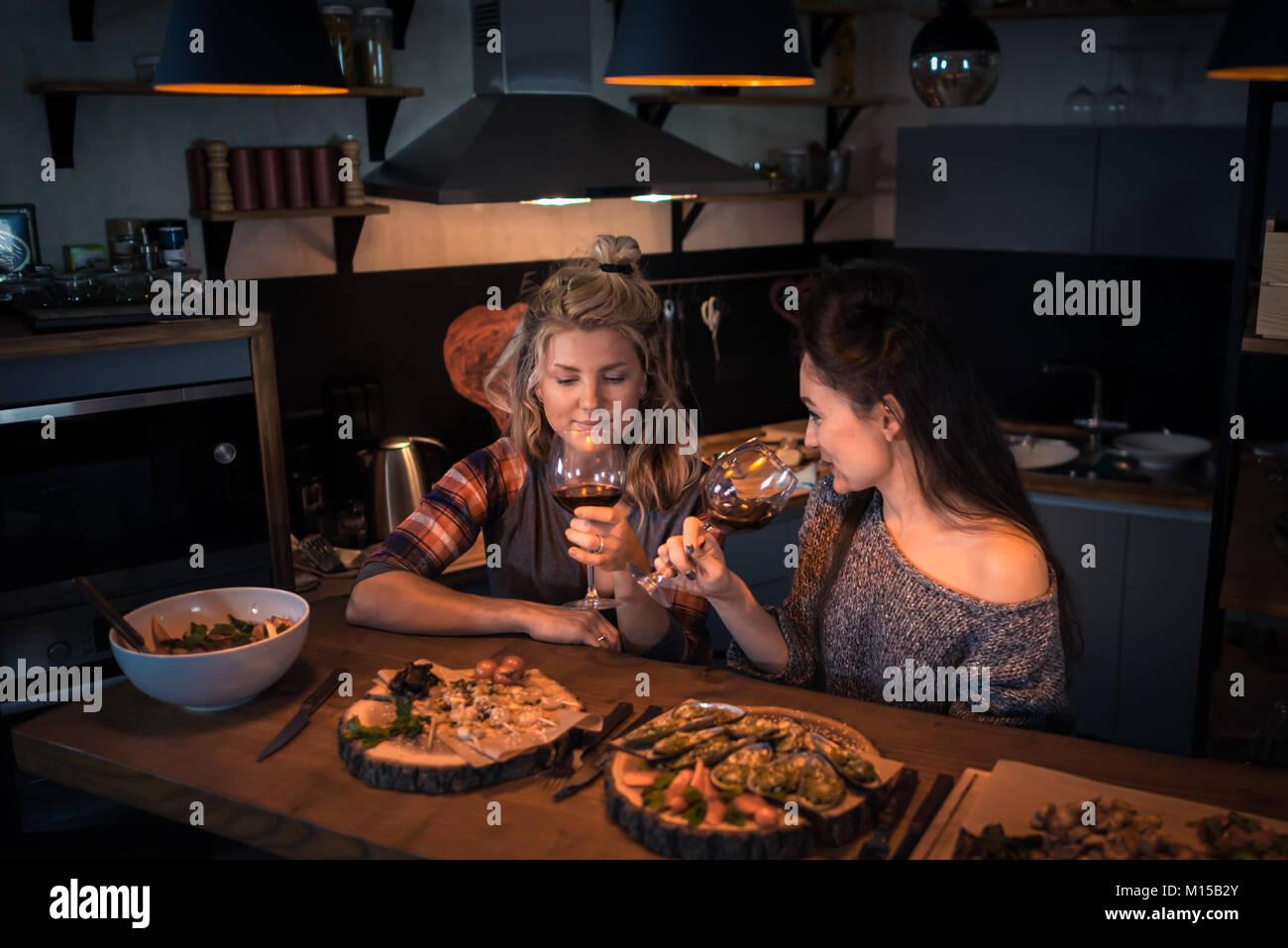 Due giovani donne seduta al tavolo con il cibo e il vino. Romantico bionda e cd51c133e2f5