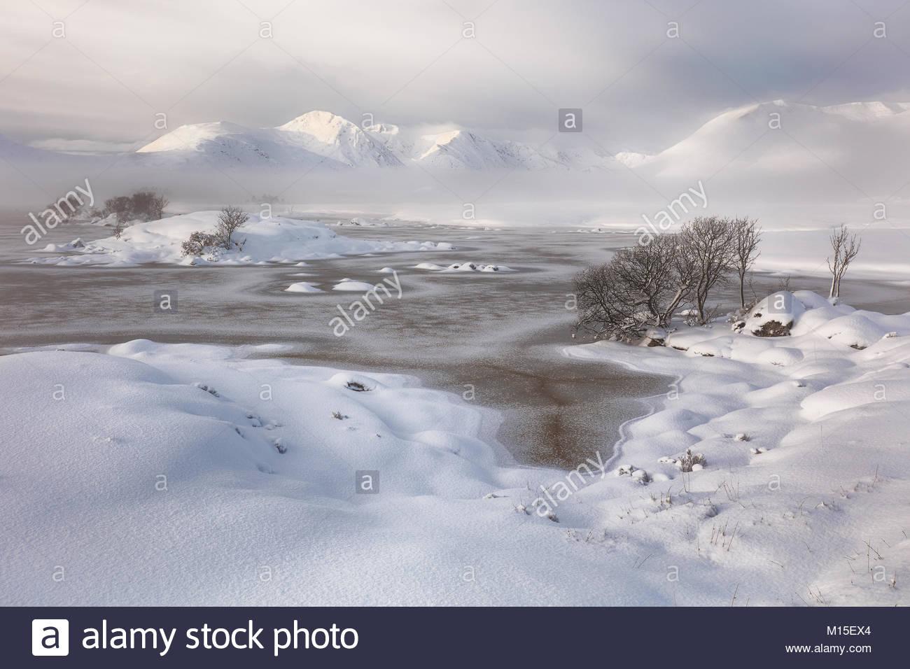 Una coperta di neve Rannoch Moor guardando sopra un congelati Lochan na h-achlaise al Misty Blackmount mountain range. Glencoe, Scozia Foto Stock