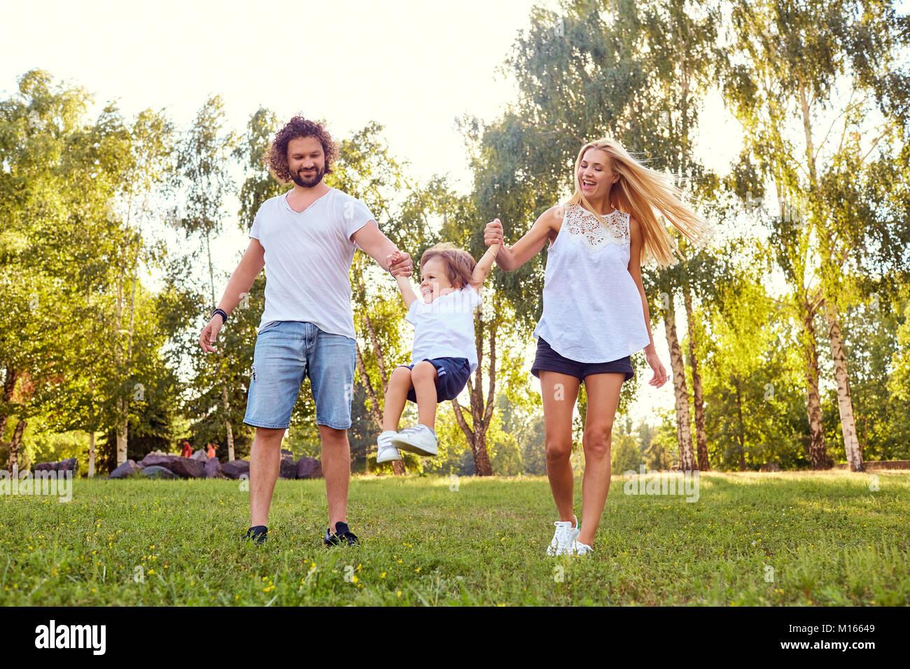 La famiglia felice nel parco. Immagini Stock