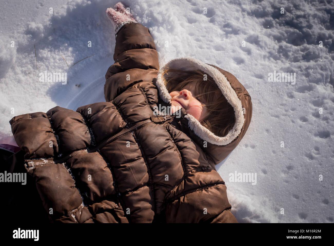 Una tre-anno vecchia ragazza fa un angelo di neve nella neve nel nordest degli Stati Uniti. Immagini Stock