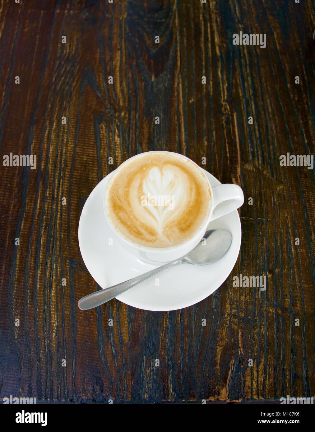 Piatto bianco caffè con pattern in schiuma con cucchiaio al buio su un sfondo di legno Immagini Stock