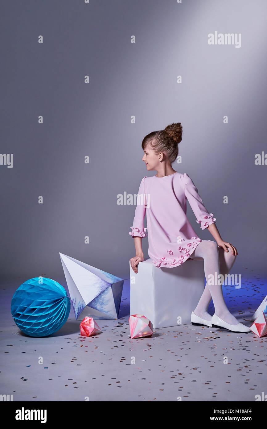 338575d8c4 Designer Collection. Origami e minimalismo. La moda dei bambini. Ragazza  nel bellissimo abito rosa . Catalogo di moda abbigliamento. Studio shot.